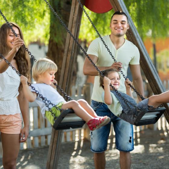 hetero parents with kids on swings