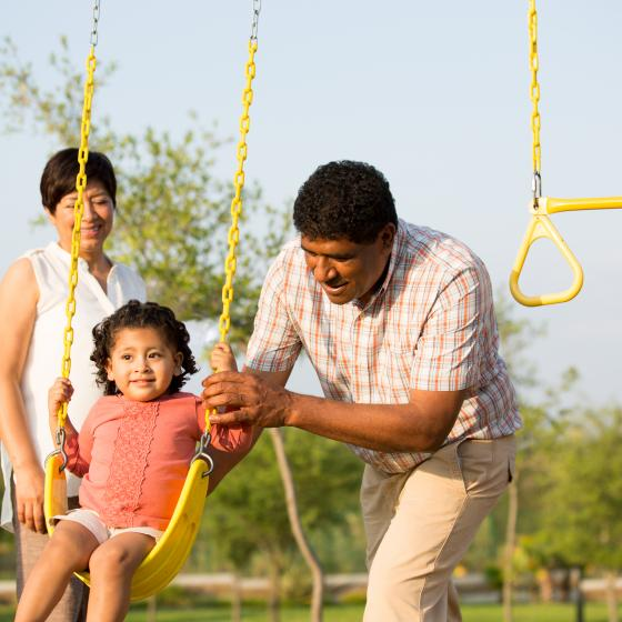parents with kid on swing